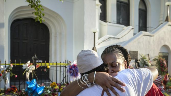Mourners Cynthia Wright-Murphy, right, hugs her sister Carolyn Wright-Porcher, right, outside the Emanuel AME Church, Saturday, June 20, 2015  in Charleston, S.C. A steady stream of people brought flowers and notes and shared somber thoughts at a growing memorial in front of the church. (AP Photo/Stephen B. Morton)