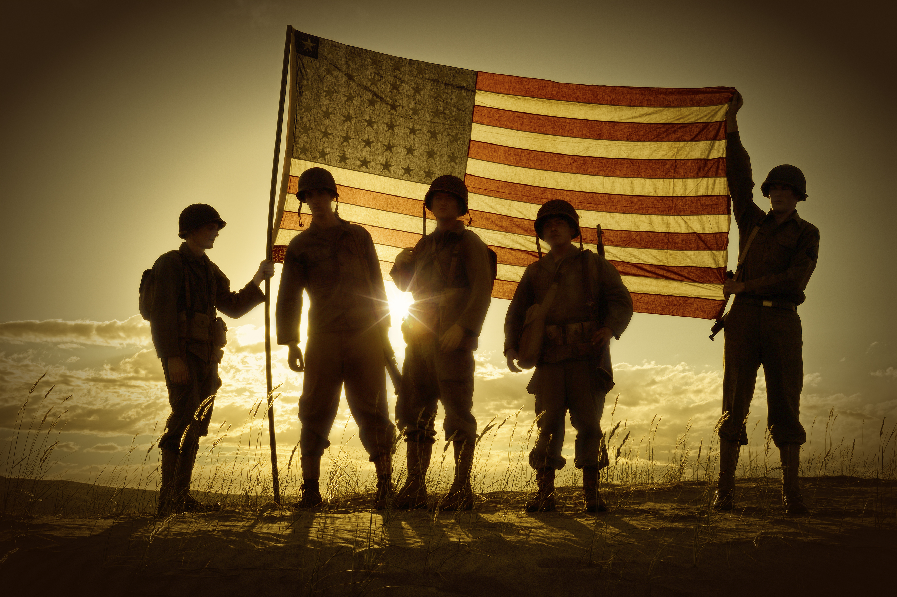 WWII Soldiers Standing In A Flag Draped Sunset - SIlhouette